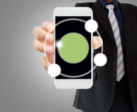businessman showing his telephone with copyspace over gray background.  photo
