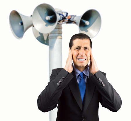 Portrait of businessman covering his ears with hand to not hear the great noise of  megaphone with negative expression in his face on white background