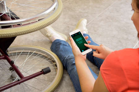 powerless: Disabled man with handicap having an accident crash with wheelchair a at home and emergency call with your smart phone. Disability concept with powerless unhelped person lying on the floor