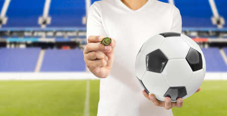Cropped image of a football player holding a soccer ball in one hand wearing white tshirt and writing ideas on a transparent wipeboard at stadium in madrid