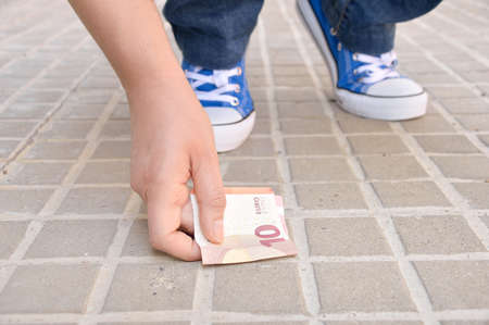 finding: cropped of lucky young crouched down finding money on the street and catching with hand