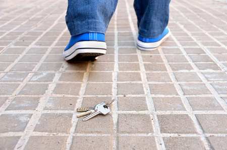 Cropped rear view of a walking young who loses the home keys on the sidewalk street in the city