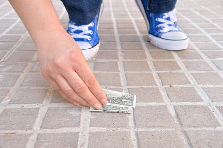 Coupé de jeunes chanceux s'accroupit en trouvant de l'argent dans la rue et prenant la main Banque d'images - 70469908