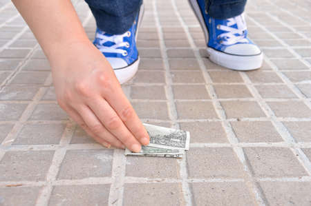 cropped of lucky young crouched down finding money on the street and catching with hand
