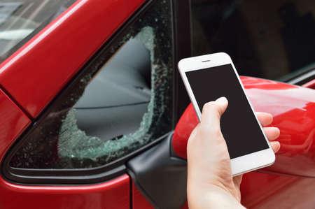 delincuencia: hombre sosteniendo el teléfono inteligente para llamar a la agencia de seguros por el vandalismo en el coche Foto de archivo