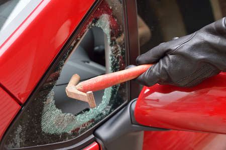 thief hitting the glass of a car to rob