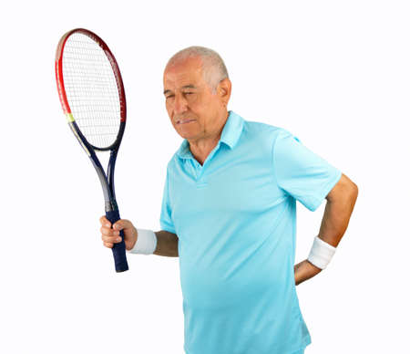 dislocation: studio shot of a senior player tennis holding the racquet and touching his lower back in pain