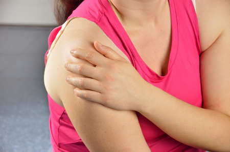 painful: Shot of a sportswoman with a shoulder injury