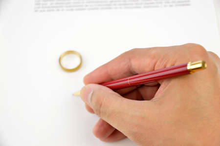 rupture: hand of a husband signing the divorce paper with wedding ring on the divorce contract