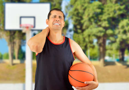 Shot of a basketball player with a neck injury over at outdoors Stock Photo