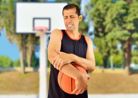 luxacion: Disparo de un jugador de baloncesto con una lesión en el codo en al aire libre