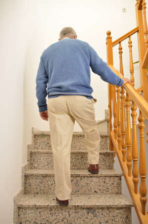성숙한 남자의 후면보기 집 계단을 등반