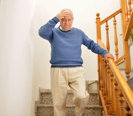 수석 남자 계단을 내려오고 인플루엔자 또는 독감에 의해 집에서 어지럼증을하는 데 스톡 콘텐츠