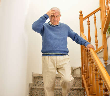 senior man coming down the stairs and having a dizziness at home by the influenza or flu Stok Fotoğraf