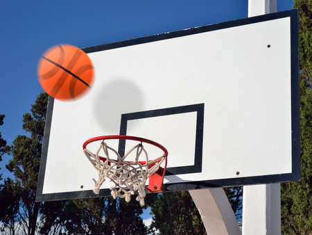 outside shooting: Scoring the winning points at a basketball game at oudoors Stock Photo