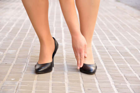 woman wearing stilettos and touching her foot bunion. Hallux valgus by use of narrow shoes