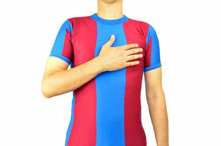 Cropped image of a young man holding a soccer ball under his arms with colors blue and red with his hand on his heart isolated on white background. Concept of love to a team or colors in sports.