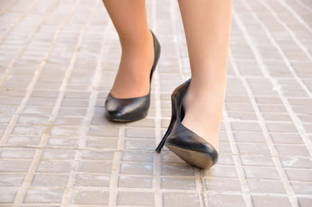 woman with twisted ankle. Female foot in pain due to sprained ankle wearing stilettos on the city sidewalk. Stock Photo