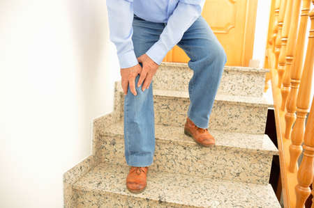rupture: elderly man walking down the stairs at home and touching his knee by the pain Stock Photo