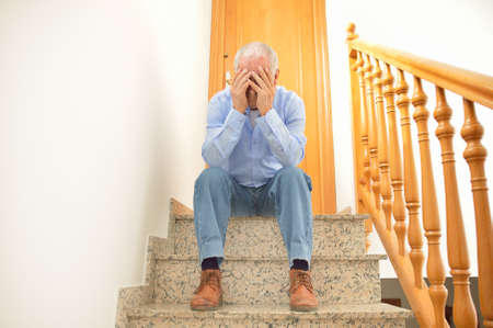 dispossession: lonely senior man sitting on the stairs of home and crying by the problems of marriage Stock Photo