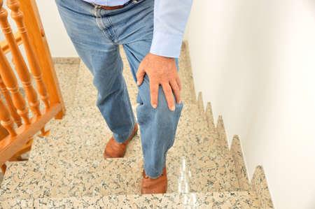 Freigegebener Schuss eines älteren Mannes, der die Treppe zu Hause hinaufgeht und sein Knie durch den Schmerz der Arthritis berührt