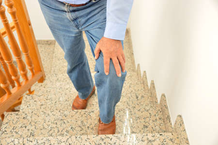 Cropped shot of a senior man going up the stairs at home and touching his knee by the pain of arthritis