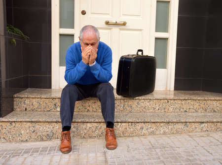 dispossession: portrait of man crying at the doorway with a suitcase as concept of divorced man