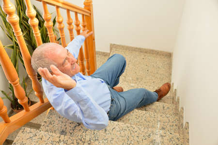 tripped: senior man falling down on stairs with hands up to try to catching the railing