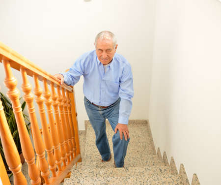 senior man going up the stairs at home and touching his knee by the pain of arthritis