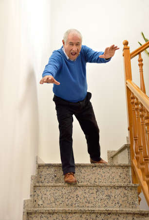 tripped: senior man falling down on the stairs Stock Photo