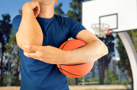 oudoors: Shot of a basketball player with a elbow injury over at oudoors