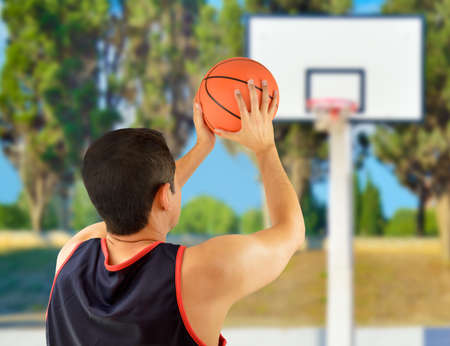 rearview: Cropped rearview of a basketball player taking free throw against at oudoors