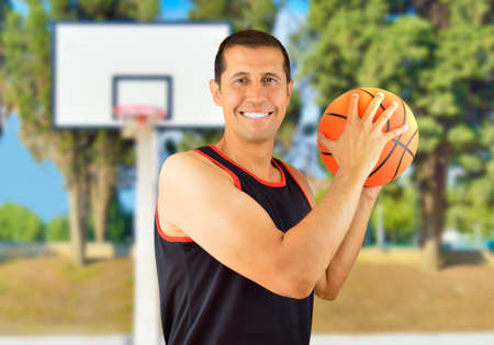 Happy man holding a basketball against at oudoors Stock Photo