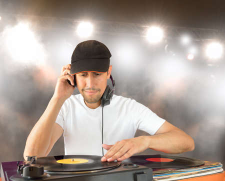 DJ mixing vinyl record on a  turntable in concert photo
