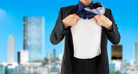 businessman superhero ripping his shirt with hands to show his real hero identity with city background Stock Photo