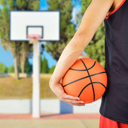 Cropped rearview of a basketball player holding a basketball against at outdoors