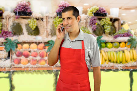 shopman with apron using a smart phone at the fruits store Stock Photo