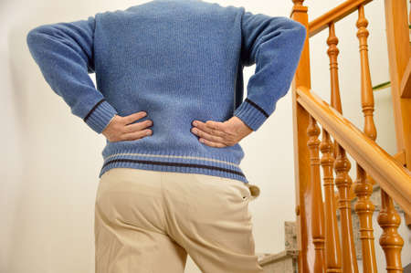 cropped shot of rear view of a senior man with lumbago pain climbing the stairs of his house Reklamní fotografie