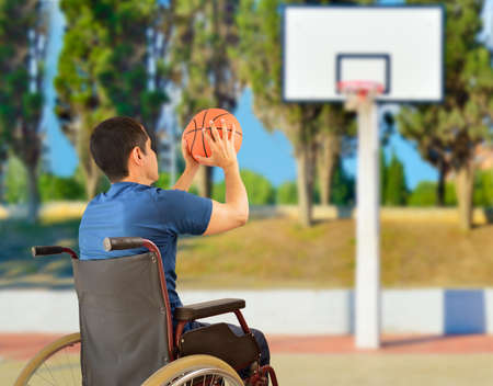 rear view of a basketball player in free throw pose in wheelchair at outdoors