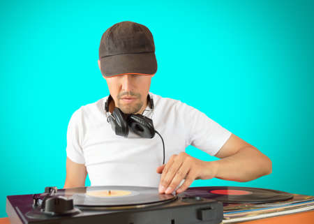DJ mixing vinyl record on a  turntable with green background Stock Photo