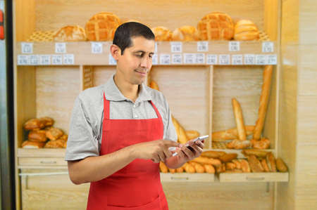 shopman male with apron uses a smart phone at the bakery