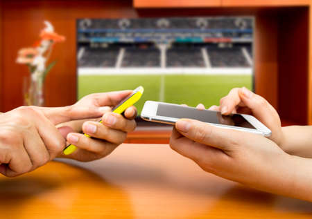 Friends using mobile phone and betting during a football or soccer match Archivio Fotografico