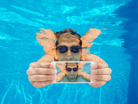 Portrait of a happy man with smart phone under water. Selfies 스톡 콘텐츠