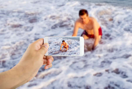 safe water: Man filming with his phone as a swimmer drowned Stock Photo