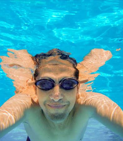 水の下でスマート フォンを持つ幸せな男の肖像画。コピー スペースと Selfies。