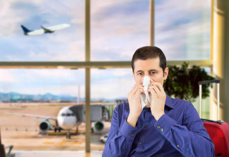 sneezing businessman sick blowing nose at airport departure lounge