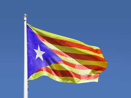 Catalan estelada flag separatist independence flag waves in blue sky Stock Photo