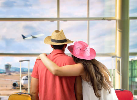 affectionate young couple in international airport looking at the airplane