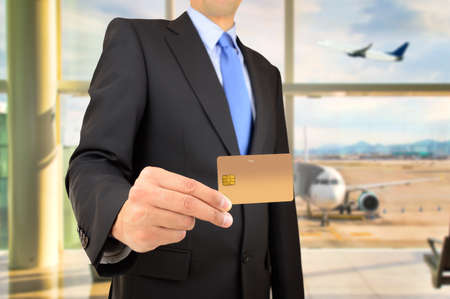 cardkey: hand of businessman showing the credit card to make a payment at airport departure lounge