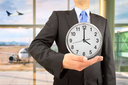 Businessman holding clock in his hand at airport departure lounge